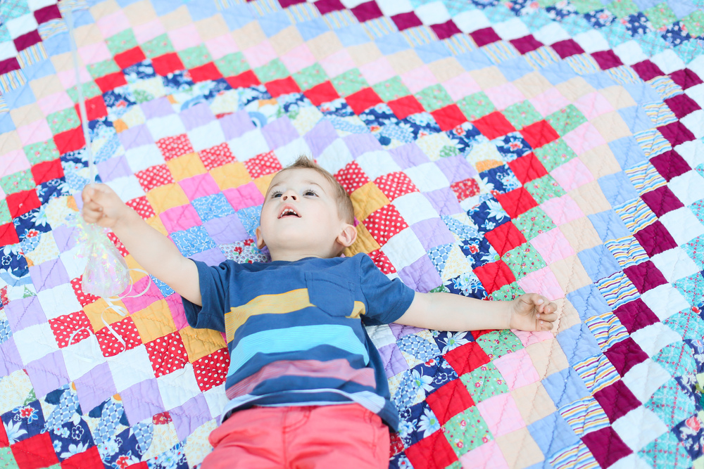 toddler boy looking up at sky on colored blanket