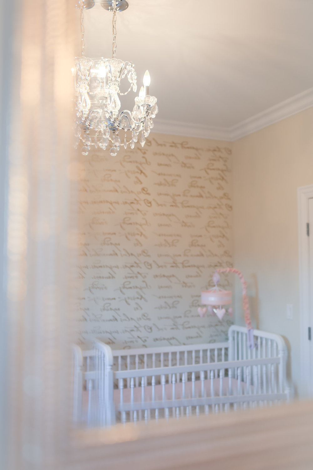 nursery chandelier and scripted wallpaper