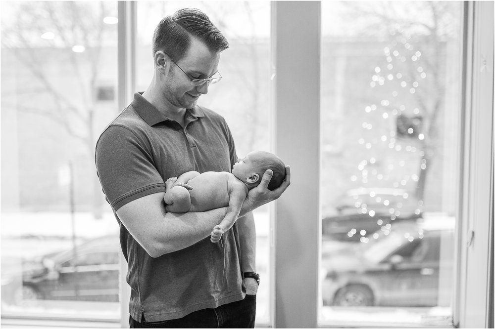 father holding newborn baby girl in window lifestyle photography image