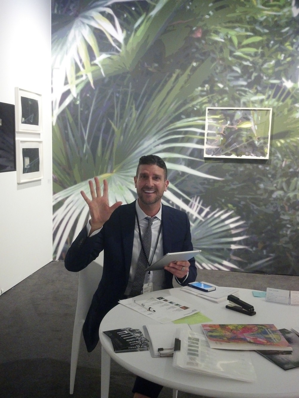 Steven Sergiovanni of Mixed Greens at work in his booth at  PULSE Miami,  featuring a wall installation by Naomi Reis.