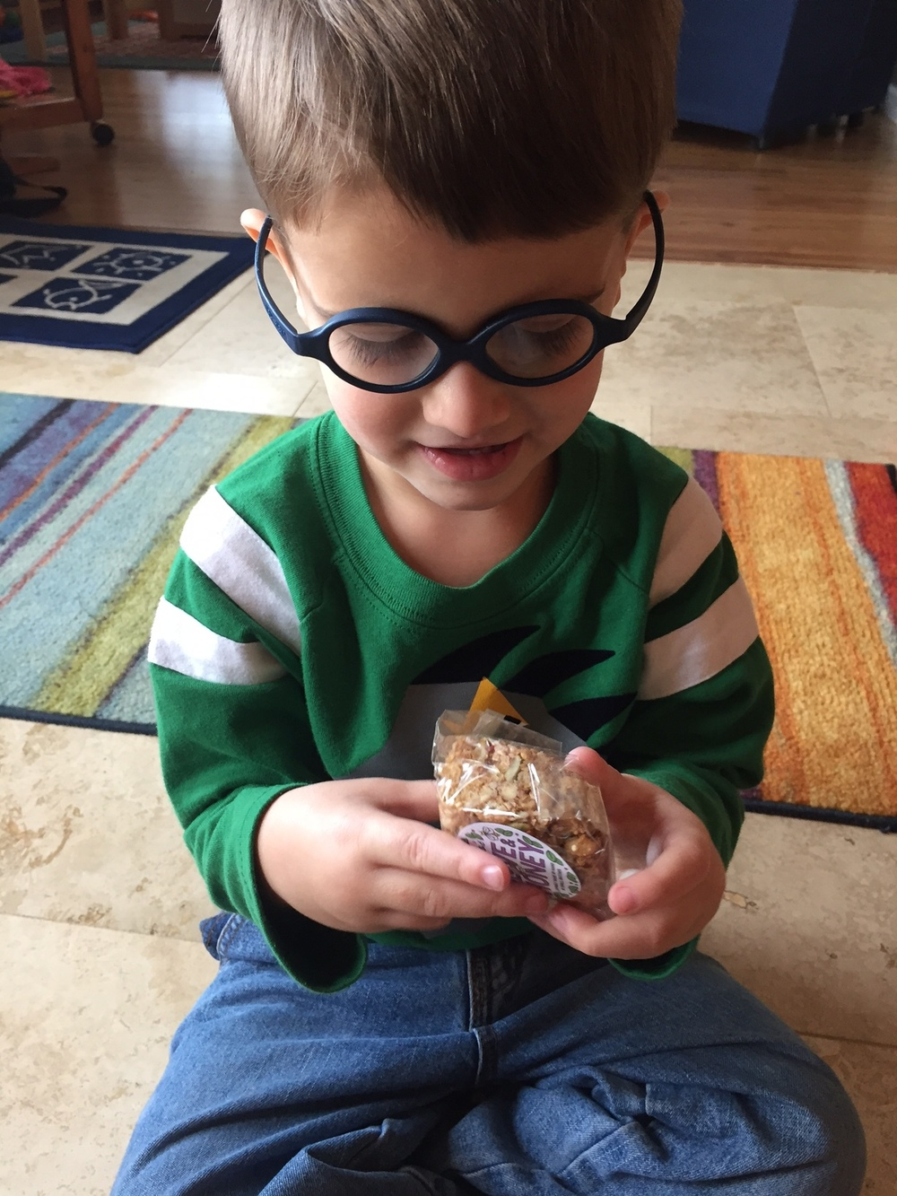 """Holly from Alaska sent this photo of her little man unwrapping a """"For Love and Honey"""" granola bar. Can he possibly be any cuter?!!"""