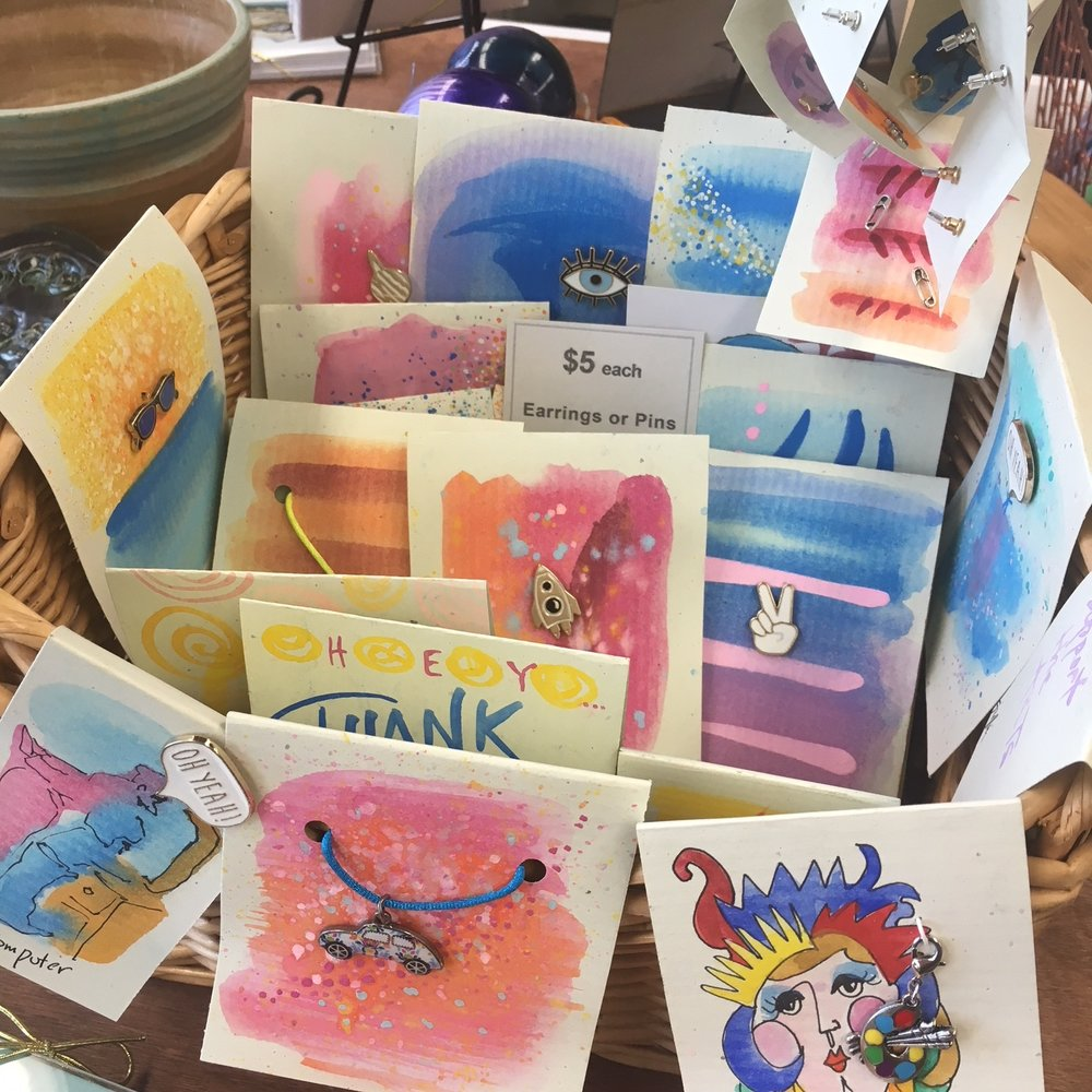 Hand-painted cards with pins or earrings or charms.