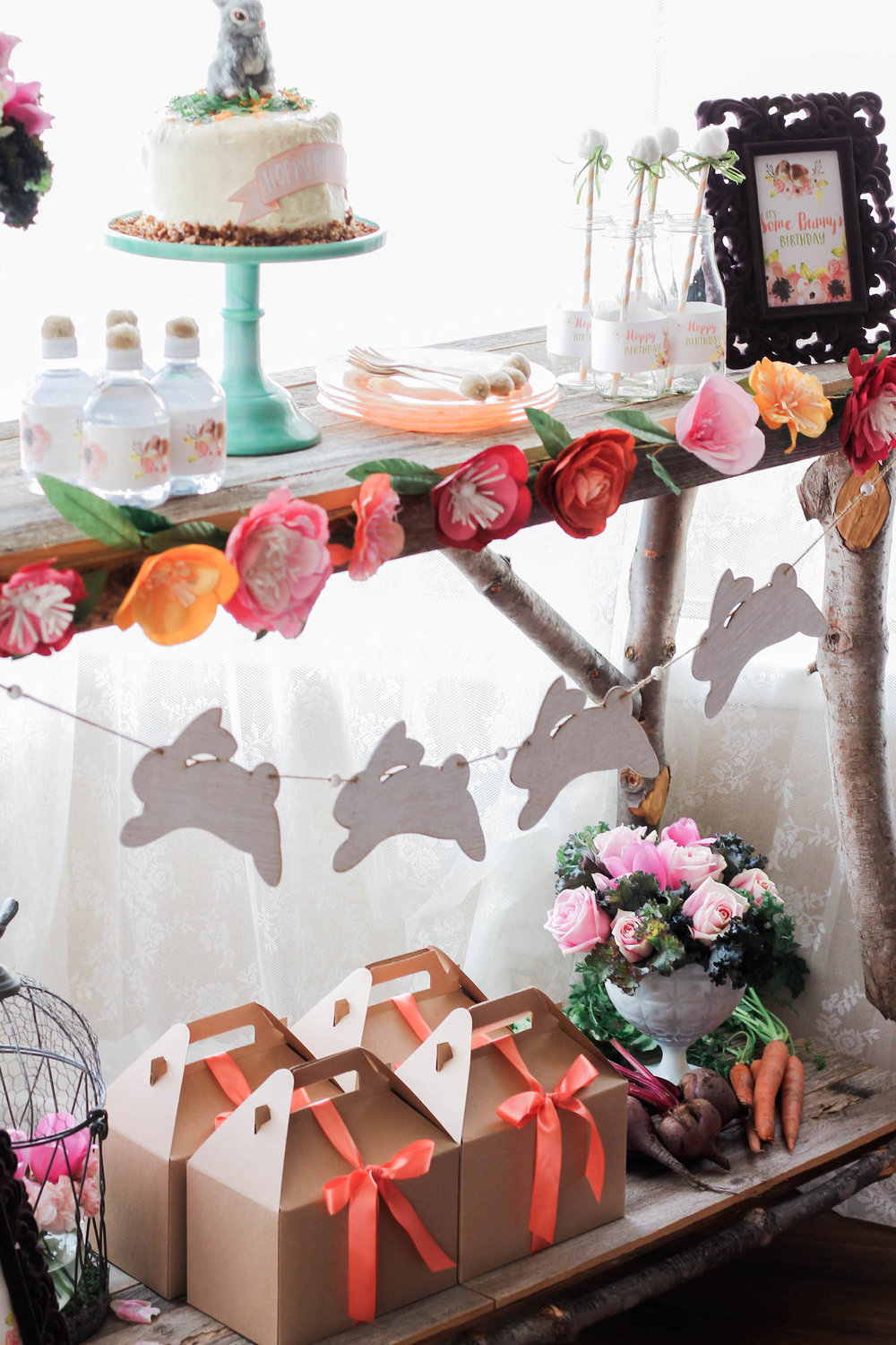 The prettiest display for a Some Bunny Spring Birthday Party - using real vegetables, wooden bunnies for a garland, paper flowers along the table edge . . . click to see more on www.GiggleHearts.com