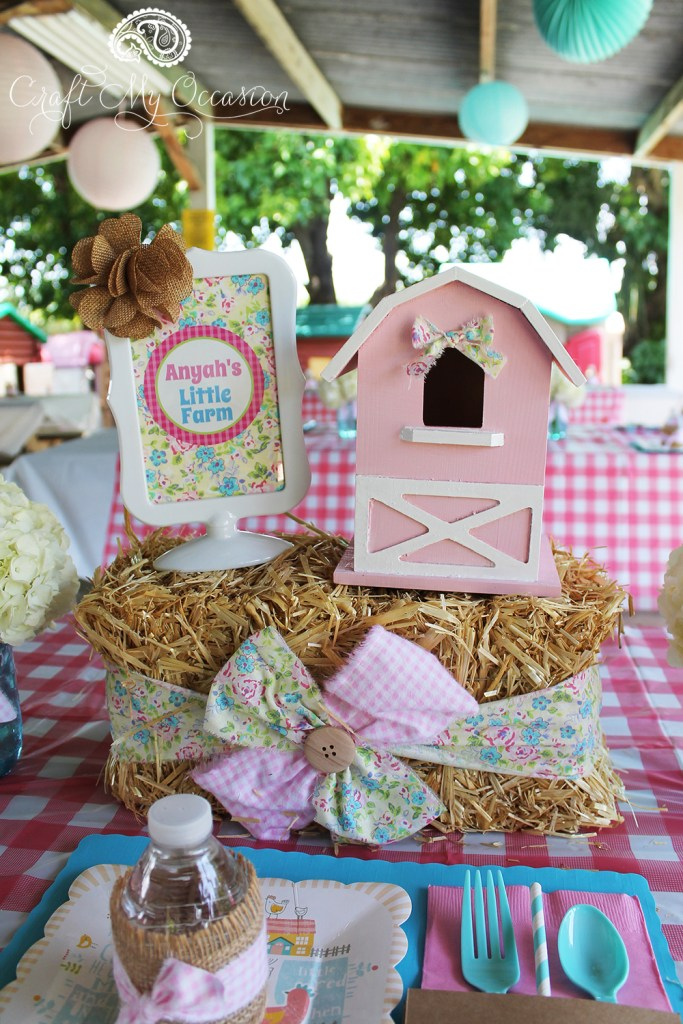 The perfect farm party centerpiece - mini hay bales with a farmhouse on top and a pretty floral framed print announcing the birthday girl's little farm. From the Pink Pony Birthday Party from Lynnette of Craft My Occasion - as seen in the Party Inspiration Gallery on www.GiggleHearts.com