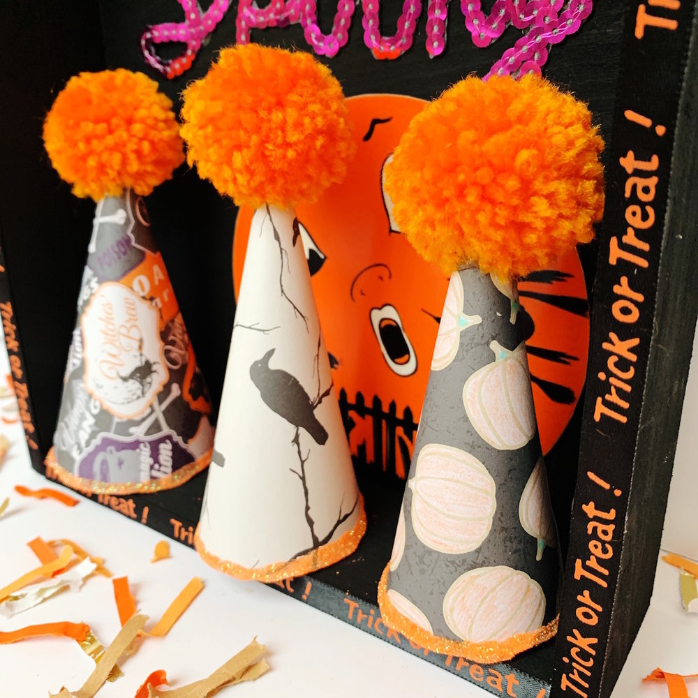 These DIY Halloween Paper Party Hats are so cute in this Halloween Shadow Box and topped with pom poms. See how to create this Halloween Mantle Decor on Giggle Hearts www.gigglehearts.com #halloweendecorations #halloween #halloweencrafts #diycrafts #halloweendecor #partyhats