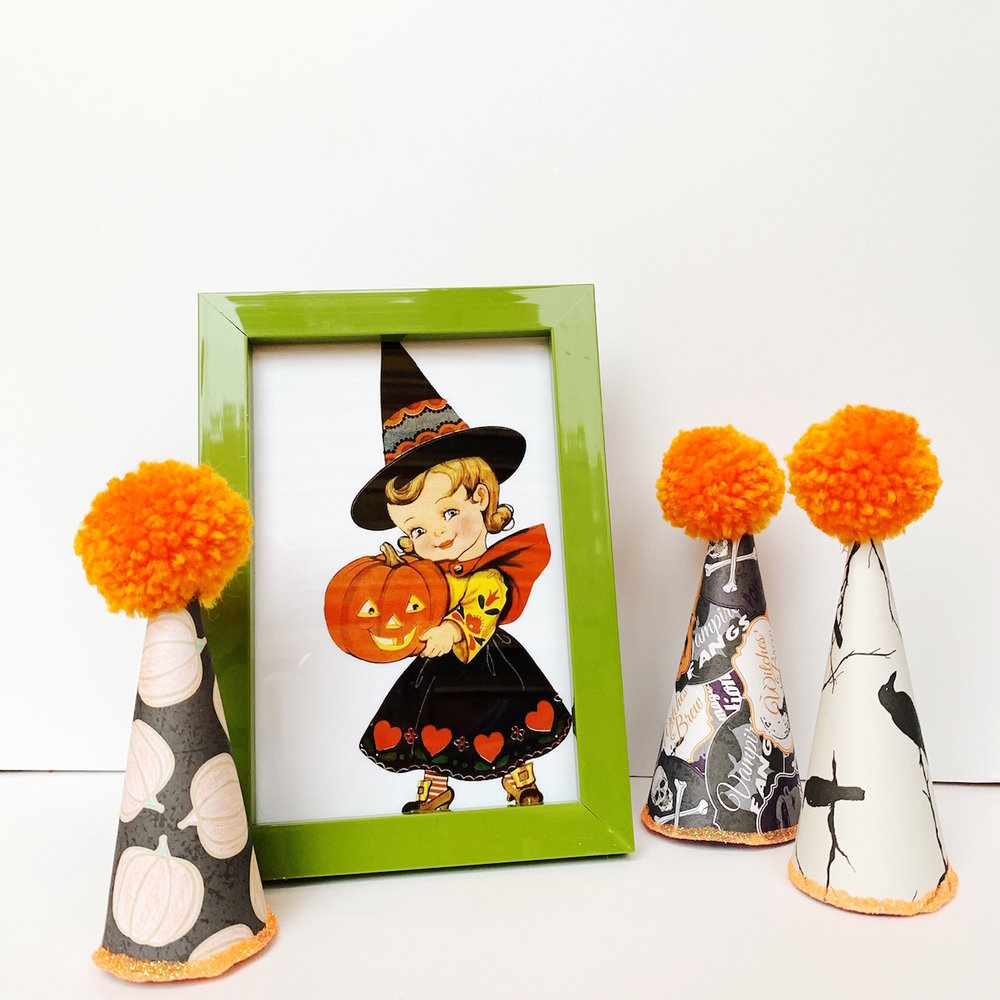 DIY Halloween Paper Party Hats are the perfect Halloween Decoration accent and look super cute next to framed Holiday Art Prints. See how to create these Halloween Hats on Giggle Hearts www.gigglehearts.com #halloweendecorations #halloween #halloweencrafts #diycrafts #halloweendecor #partyhats
