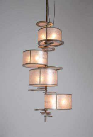 In this modified version of the crankshaft light fixture, an additional drum was added along the vertical axis. The fixture's smaller drums and lighter color scheme produces an amber glow.