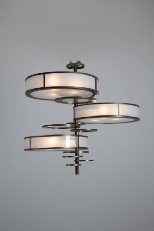 The original crankshaft light fixture features three wide light-diffusing lenses and an array of circular metal accents arranged around a narrow central base.