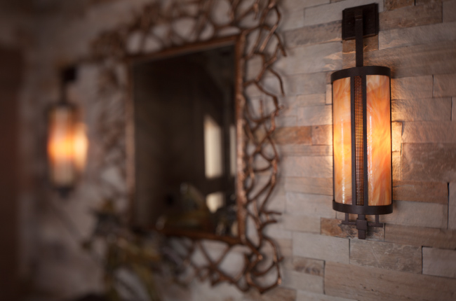Accent lighting keeps the home's warm transitional feel a constant theme. Hammerton's contemporary indoor sconces sport a dark art glass diffuser, fine mesh accents and a River Rust finish.