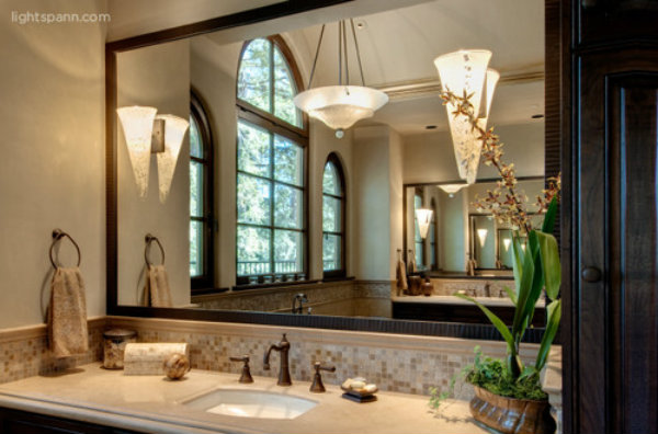 Two contemporary wall sconces and a central chandelier can brighten up an expansive mirror, as well as a vanity countertop.