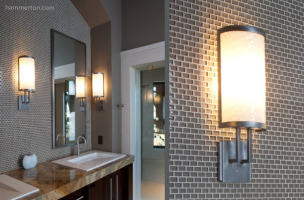 Sleek wall sconces that exude a flattering, yellow glow can add warmth and vitality to an ultra-contemporary bathroom.