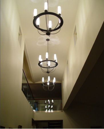 A row of contemporary light fixtures adds both functionality and aesthetic appeal to long, dark entryways.