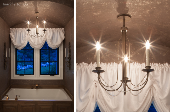 A delicate candle-style light fixture adds a luxurious and sophisticated touch above a cozy tub.