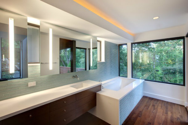 Fluorescent lights inset into the mirrors of this master bath provide lighting at face level, while also creating a sense of serenity and warmth.