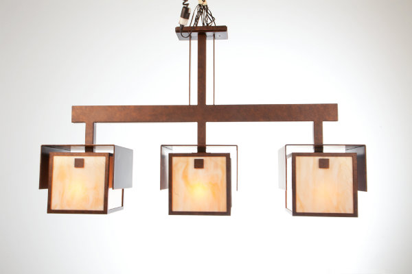 This unique suspension light, crafted from artisan glass with an antique copper finish, is stunning in its symmetry and simplicity. The fluidity and clean craftsmanship of this piece celebrates the essential ideologies of Arts & Crafts design.