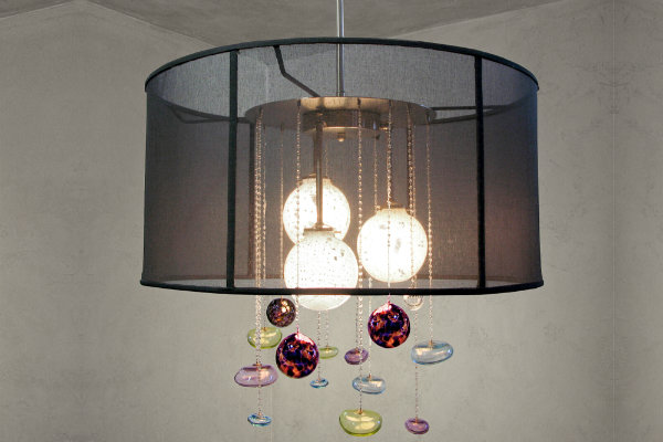 An eclectic twist on the traditional drum fixture, this Lightspann Aurora Chandelier features vintage light bulbs gleaming behind a sheer black shade, accented with a whimsically colorful shower of blown glass baubles.