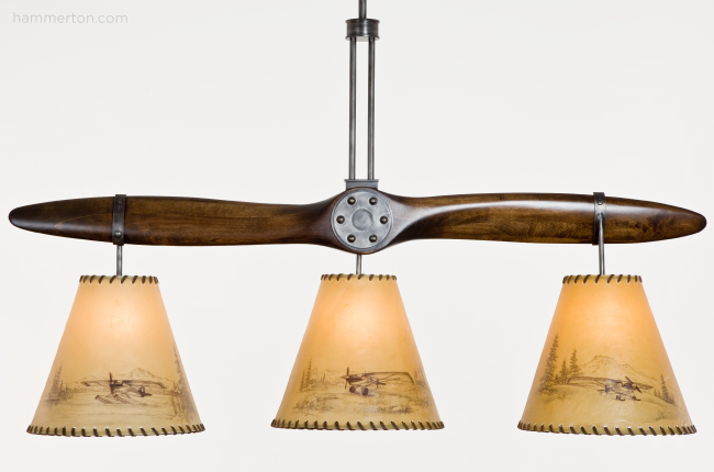 This bar light designed for a recreational pilot makes clever use of a vintage Cub aircraft propeller. The rawhide shades feature hand-inked drawings of three different vintage airplanes.