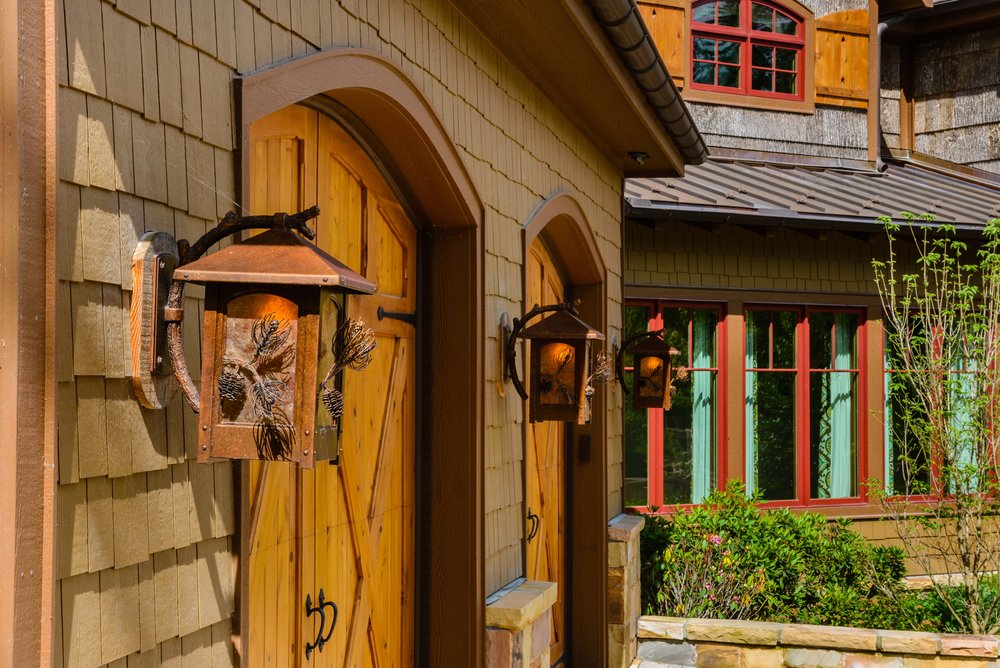 Rustic outdoor sconces with pine motif adorn this Lake Toxaway retreat garage by architect  C. Allen Brown  | Cashiers, NC