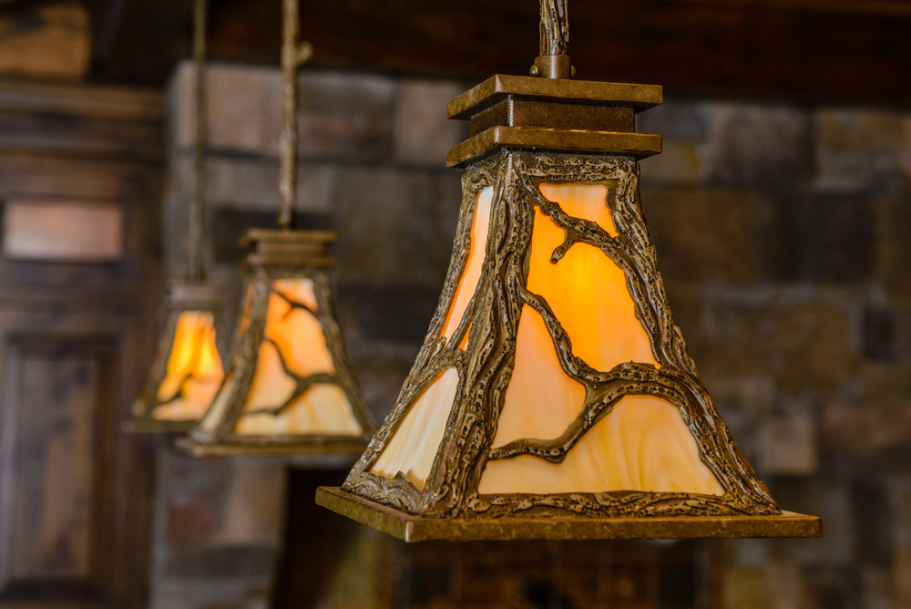 A trio of LA7130 rustic pendants feature detailed tree branch motif and wood texture.