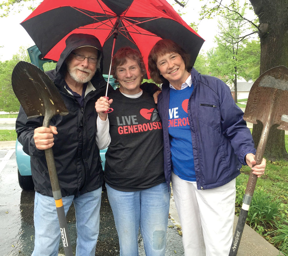 Dave Western, Linda Schroeder, and Liz Cooper take a moment to get out of the rain.