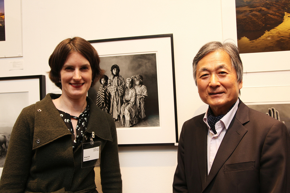Founder of FWAB.org,   Kenro Izu   with volunteer Magarit Erb,   photograph by   Irving Penn   in background.