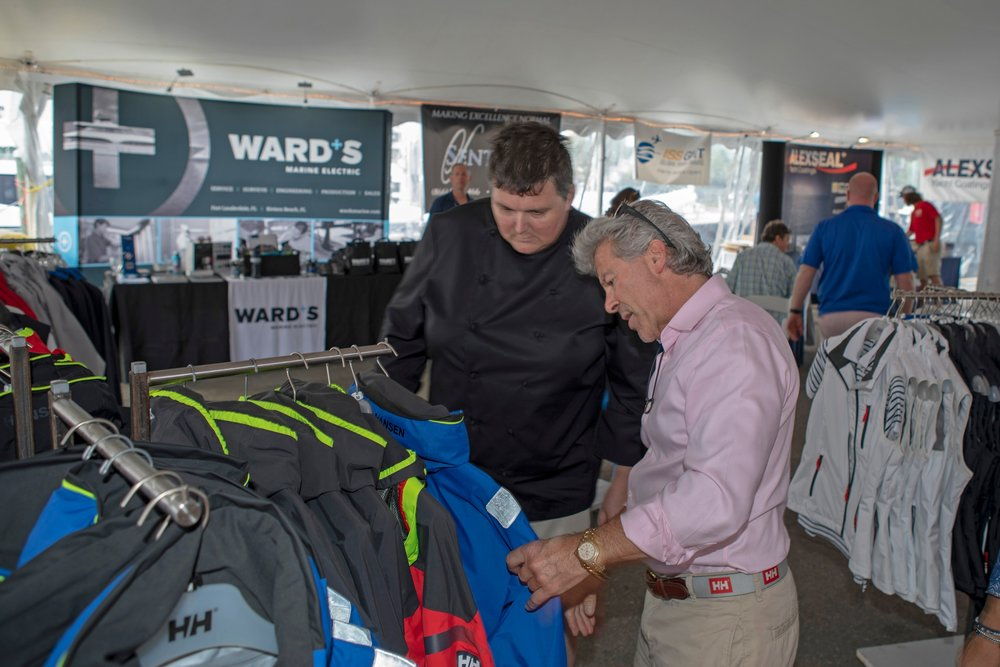Jay Lasky, owner of Helly Hansen Newport, shows chef Shaun Byers of the M/Y  Domani  Helly Hansen gear at the Newport Charter Show.