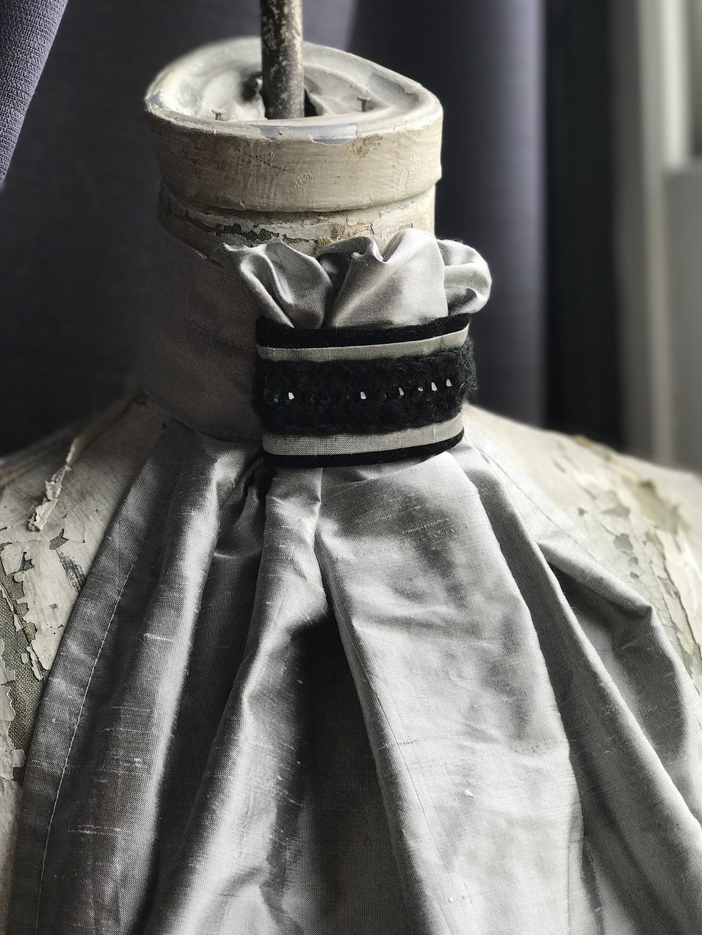 Gray silk tie with Italian woven crystal piece adorning neck