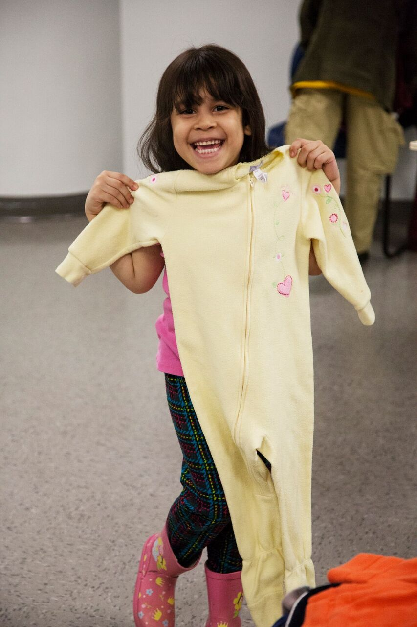 A child shows off the pajamas she received