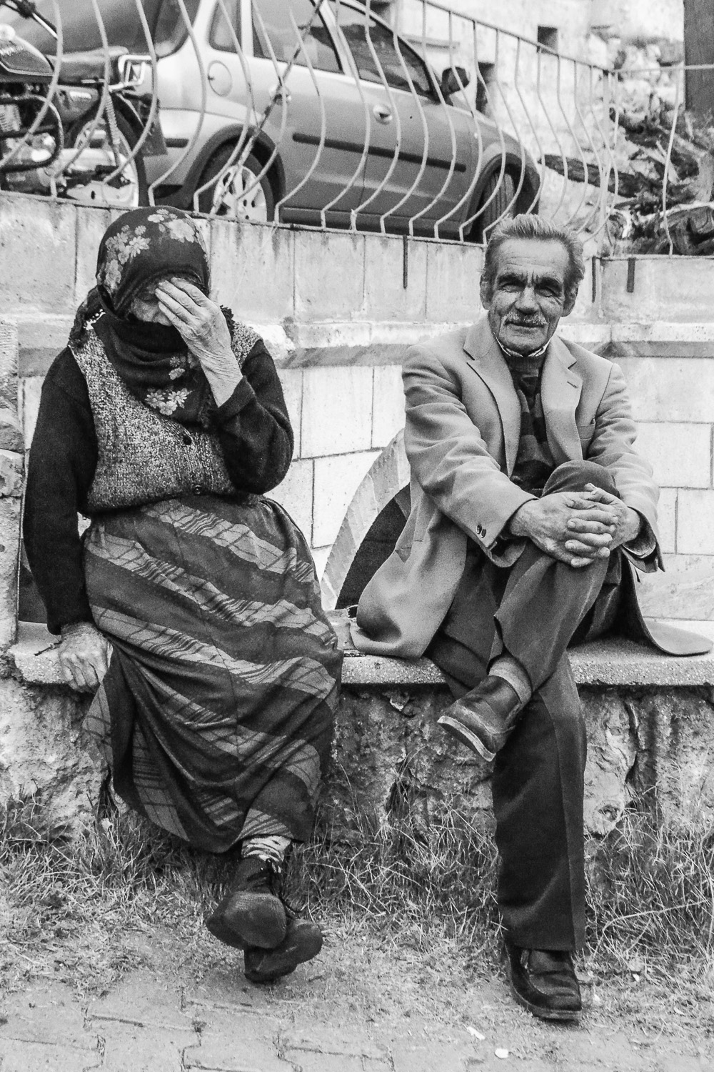 a woman and man sit in goreme, turkey. as seen here, some women believe that showing their face in a photo goes against religious beliefs