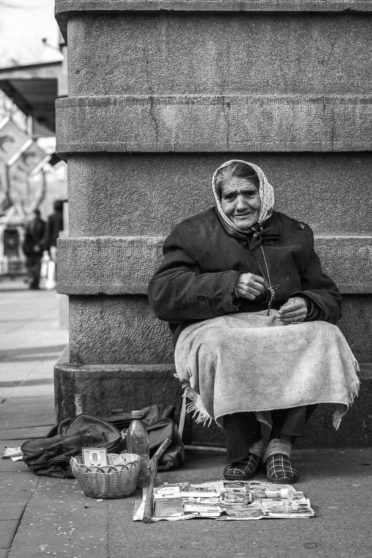 an elderly woman sells trinkets and begs in belgrade, serbia