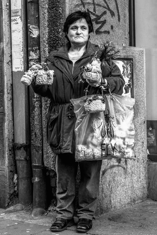 a woman sells trinkets on the street of sarajevo, bosnia