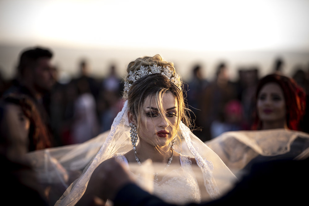 A Yazidi Wedding:  The marriage of Amera and Samir took place just outside the Bajed Kandala camp. Several hundred from the community attended the traditional celebration, dancing throughout the day and evening. When night fell everyone returned to the camp and tents they've called home since 2014.