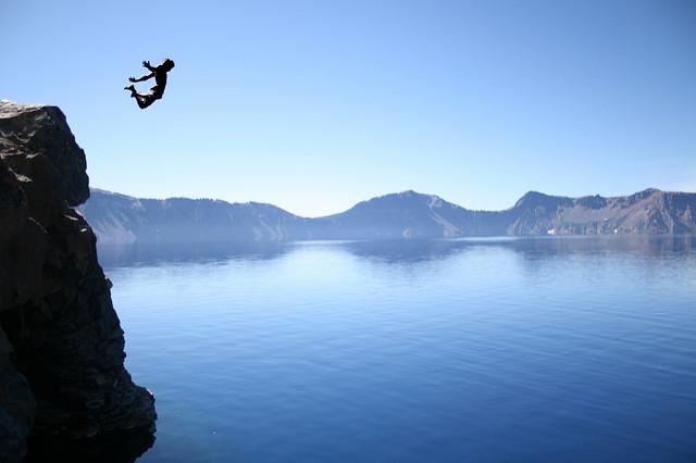 man jumping in mid air - coasteering deep water cliff jump