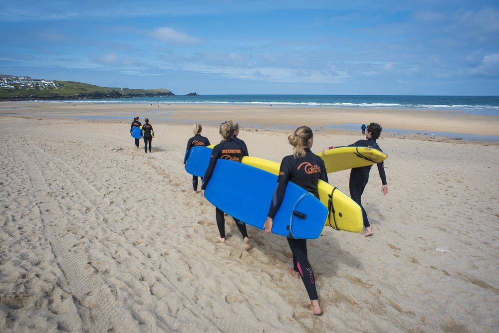 students with wetsuits and surfboards walking to their on a surf lesson at fistral beach newquay cornwall