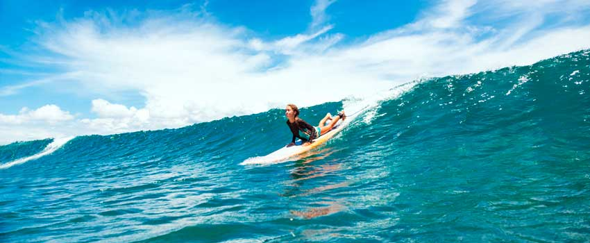 surfer girl popping up a big blue wave