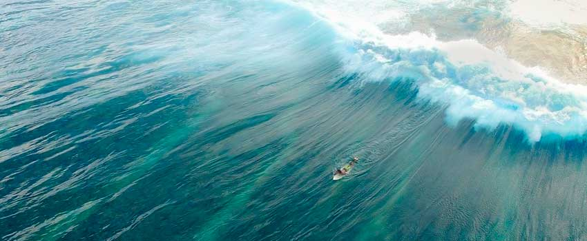 Ariel view of surfer paddling out to to sea