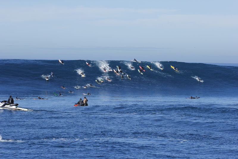 BIG WAVE SURFERS PADDLING