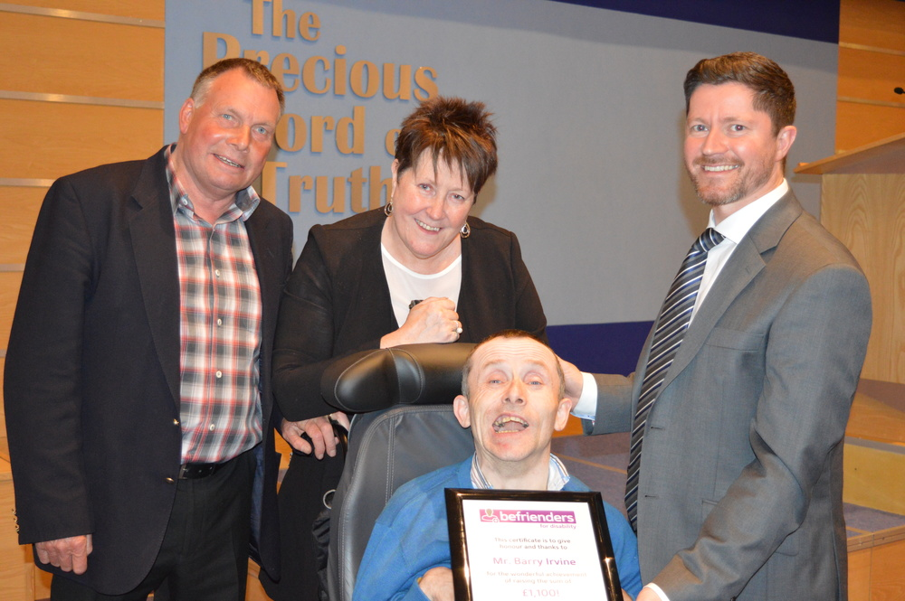 Barry (centre foreground) with Raymond (left) who drives the bus he takes to get to church and was instrumental in helping to secure sponsorship. Barry was presented with his certificate by Mrs Terry Fairfowl (centre) and Pastor David Murray, two of the Directors of Befrienders For Disability.