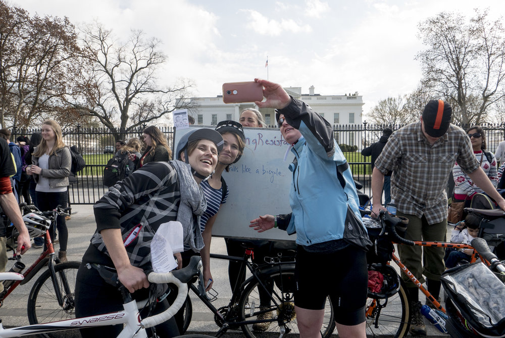 "Leigh Ann, board member of  HIPS  (Rolling Resistance beneficiary), and team members visit the White House checkpoint where they had to answer ""Who were the first people to picket the White House?"" and we're encouraged to leave a message to the new resident."