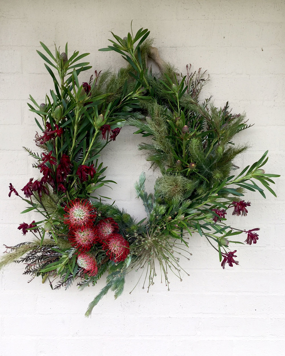 Classic Christmas Wreath featuring natural green foliage and a touch of red from $95