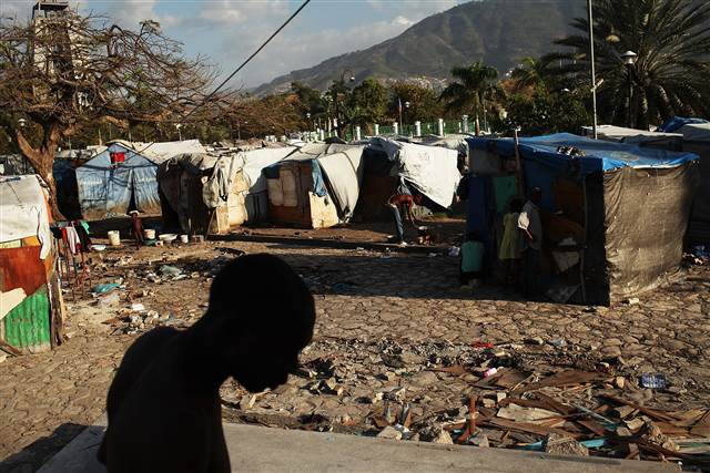 A man walks past a camp for people displaced by the earthquake on March 4, 2012 in Port-au-Prince.