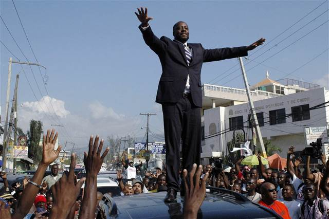 Haiti hip-hop star Wyclef Jean greets the crowd before officially registering as a presidential candidate at an office in the Delmas neighborhood of Port-au-Prince in 2010.