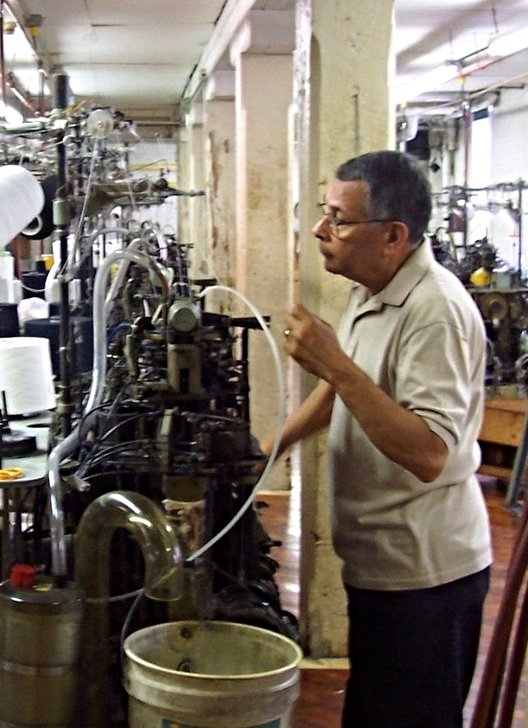"My father, Ashvin Jayantilal Chudgar, working on a machine called an ""Amy knitter"" at Keystone Hosiery."