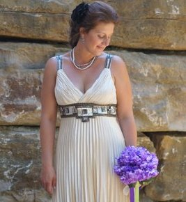 Debbie - bride in front of stones with purple flowers.jpg