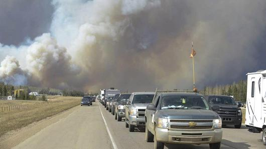 Evacuees flee from a raging wildfire in Fort McMurray, Alberta on Tuesday. Source: Greg Halinda,The Canadian Press,AP
