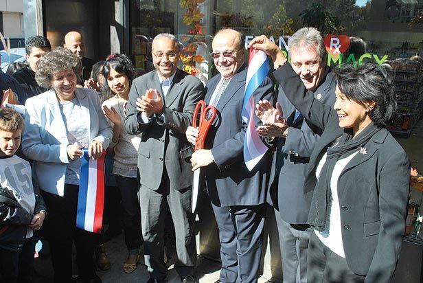 PHOTO BY KHORRI ATKINSON    Celebrating the reopening of Frank's Pharmacy in Jackson Heights are owner Frank Buonagurio, with scissors, his wife, Nidia Fortuna-Buonagurio, right, state Sen. Jose Peralta, Councilman Danny Dromm and other supporters.