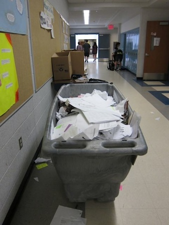 Large gondola filled with paper recycling in school hallway.