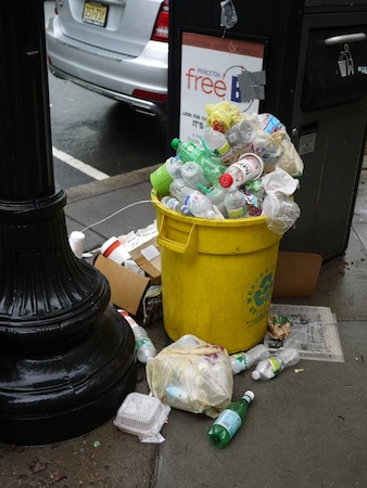 A yellow recycling bin overflowing with bottles and cans on Nassau Street the day after Communiversity