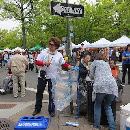 Volunteer changing a recycling bin liner at a busy street corner