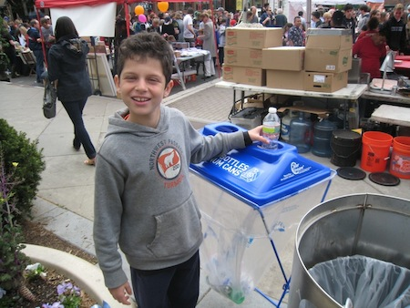 A boy drops a plastic bottle into a recycling bin at Communiversity event.